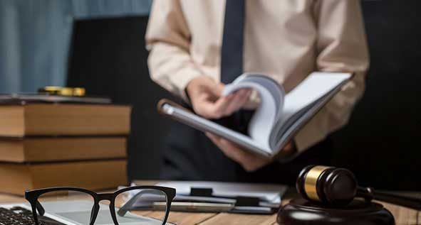 Business lawyer working hard at office desk workplace with book and documents